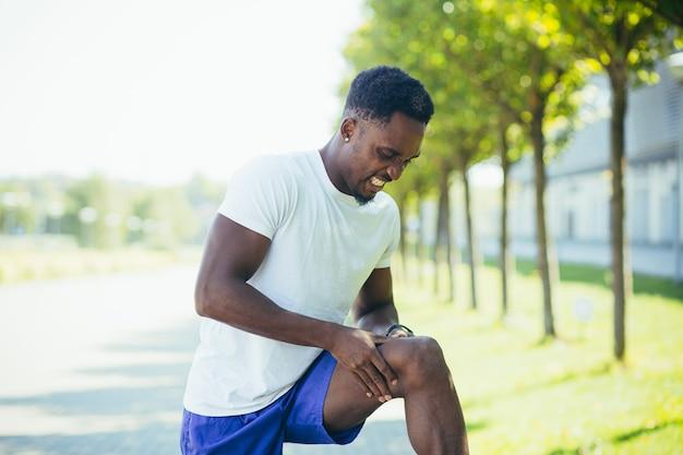 L'uomo ha forti dolori alle ginocchia e ai muscoli delle gambe dopo l'allenamento e la corsa, dolore da spasmo