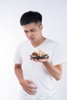Un uomo ha un mal di stomaco dopo aver mangiato deliziosi zongzi (gnocco di riso) su dragon boat festival, cibo tradizionale asiatico, sfondo bianco