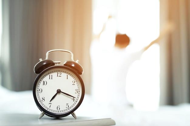 L'uomo odia svegliarsi presto la mattina. ragazza sonnolenta guardando la sveglia e cercando di nascondersi sotto il cuscino