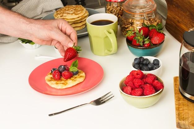 Uomo che fa colazione con una tazza di caffè e frittelle con frutti di bosco sul bancone della cucina