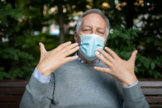 Uomo che ha difficoltà a respirare con la maschera, prevenzione del coronavirus nel concetto di climi caldi