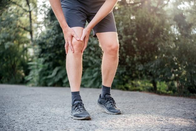 Un uomo che ha difficoltà a raddrizzare o piegare il ginocchio a causa della borsite