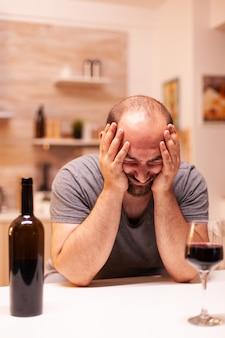 Uomo che ha problemi emotivi seduto da solo in cucina con un bicchiere di vino rosso sul tavolo. malattia della persona infelice e ansia che si sente esausta per avere problemi di alcolismo.