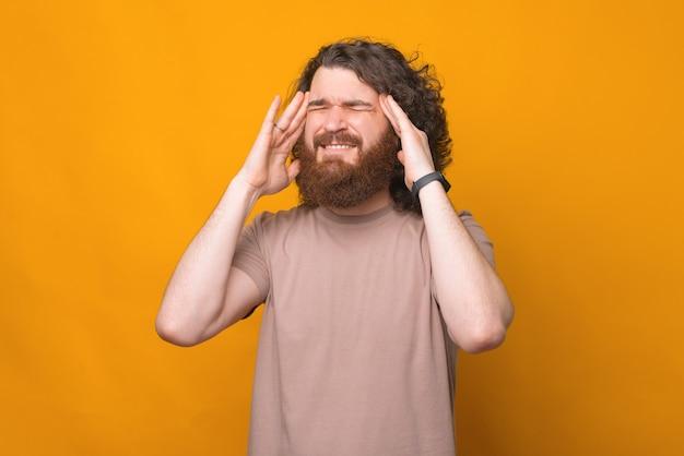 Uomo che ha mal di testa e gesticolando su giallo