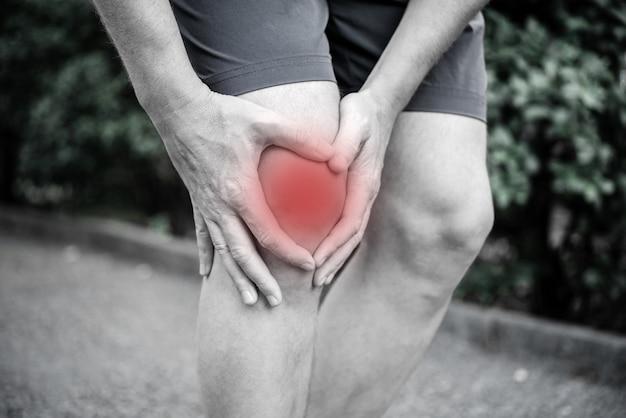 Un uomo con infiammazione e gonfiore al ginocchio tendinite lesione al ginocchio