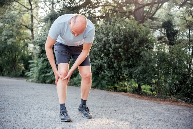 Un uomo che ha un dolore intenso nella parte anteriore del ginocchio