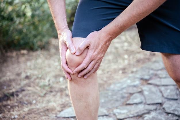 Uomo che ha dolore al ginocchio durante l'esercizio del trattamento del trauma al ginocchio