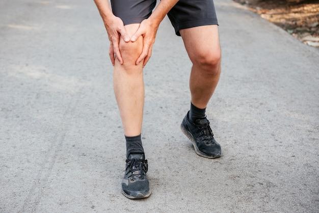 Un uomo che ha un ginocchio quando corre o fa jogging