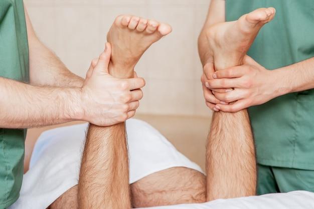 Uomo con massaggio alle gambe in piedi da due massaggiatori.