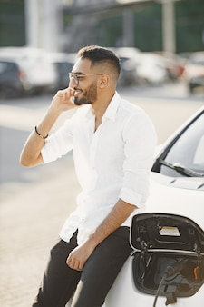 Uomo che parla al cellulare mentre aspetta l'auto elettrica. stazione di ricarica, auto ecologiche. etnia araba.