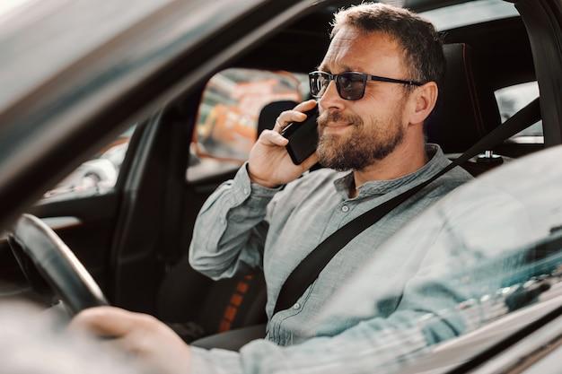 Uomo che ha una conversazione telefonica mentre si guida l'auto.