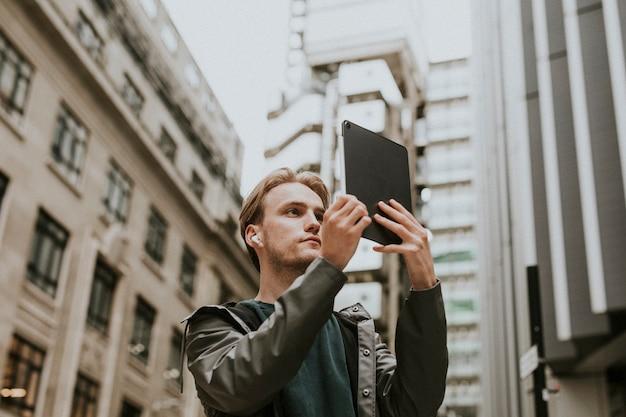 Uomo che fa una videochiamata sul suo tablet digitale in una città