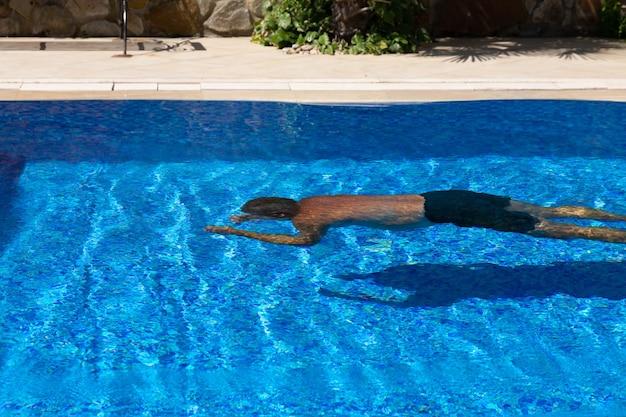 Un uomo in costume da bagno in stile hawaiano nuota sott'acqua in una pozza di acqua blu. il concetto di divertimento in piscina in vacanza.