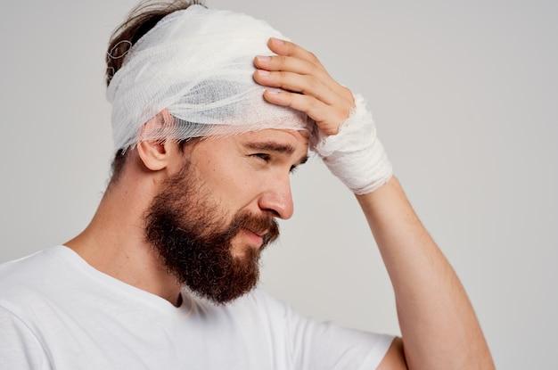 Uomo con lesioni alla testa e al braccio problemi di salute sfondo chiaro