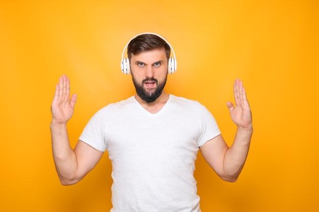 Un uomo in cuffia che ascolta musica, mostra le mani in alto.
