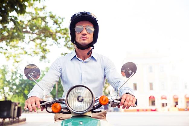 Uomo in casco cavalcando scooter