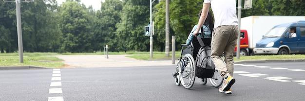 Uomo che aiuta una donna disabile a muoversi in sedia a rotelle sulla strada