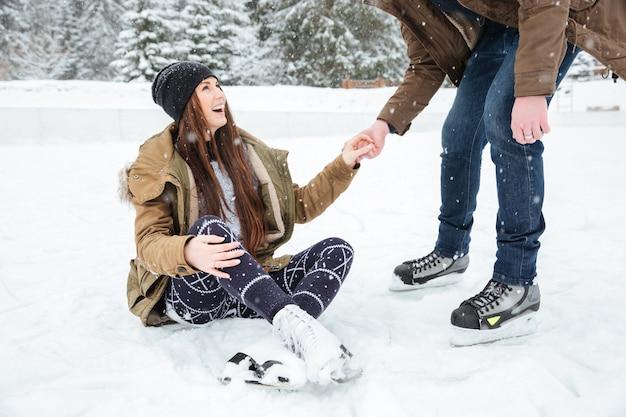 Uomo che aiuta la ragazza a stare in piedi sulla pista di pattinaggio all'aperto