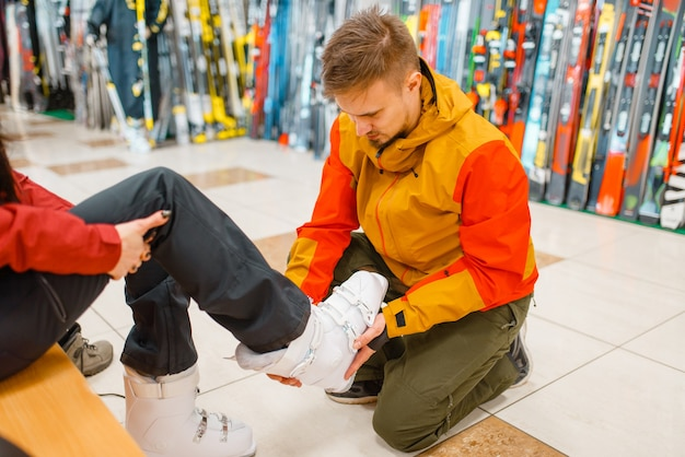 L'uomo aiuta la donna a provare scarponi da sci o snowboard, fare acquisti nel negozio di articoli sportivi. stile di vita estremo durante la stagione invernale, negozio per il tempo libero attivo, acquirenti che scelgono attrezzature protettive