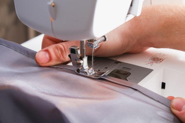 Uomo orlo una tenda su una macchina da cucire. cucito, hobby, hobby, miglioramento domestico.
