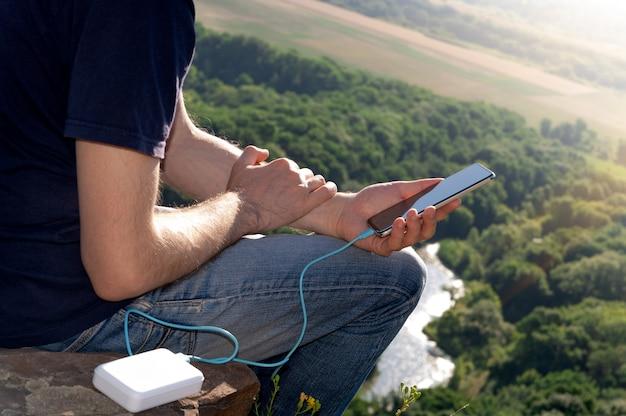 L'uomo in escursione usa lo smartphone durante la ricarica dal power bank sulla roccia all'alba
