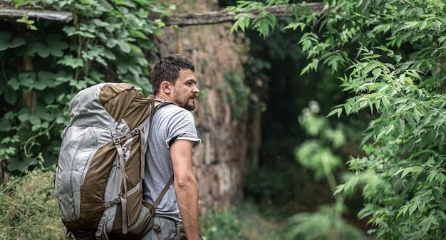Un uomo in escursione con un grande zaino viaggia nella foresta.