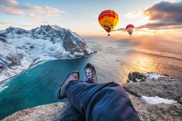 Uomo escursionista gambe incrociate seduto sulla cresta rocciosa con mongolfiera che vola sull'oceano al tramonto