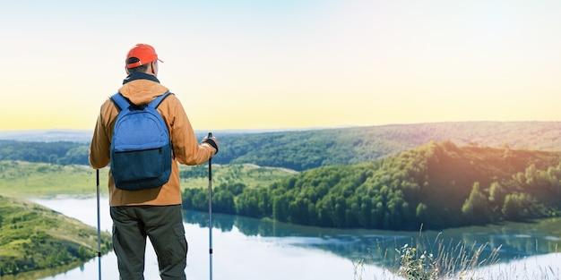 Viandante dell'uomo che pensa sul picco di montagna e guarda il tramonto o l'alba. banner panoramico dell'uomo che fa un'escursione in estate.