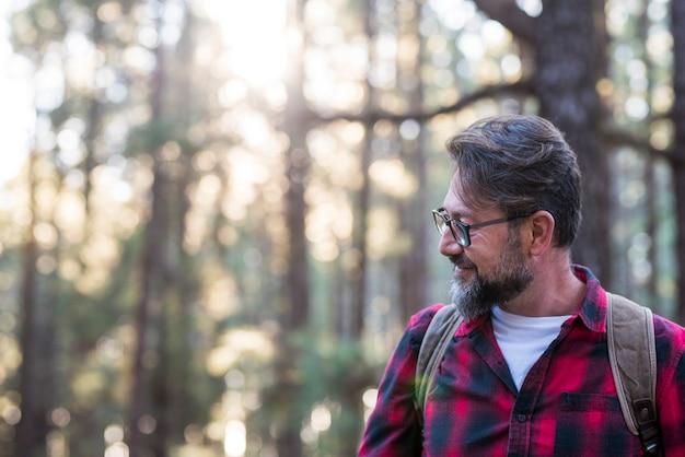 Uomo che cammina e si diverte in un bosco posizione nella foresta vista laterale di un uomo che indossa una borsa che cammina attraverso una foresta felice adulto giovane maschio caucasico ritratto godendo natura sana stile di vita tempo libero