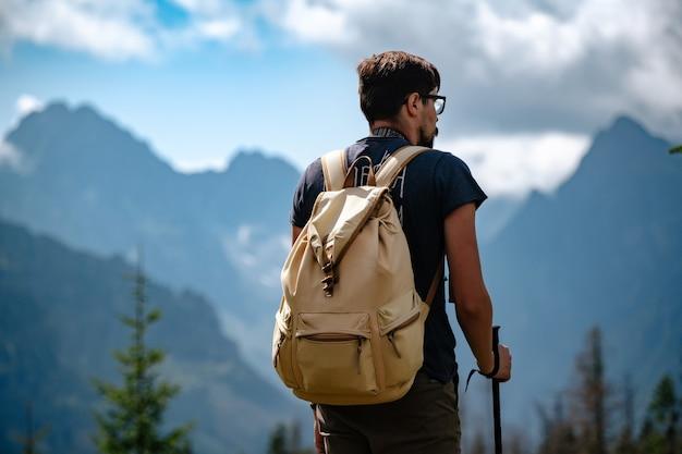 Uomo che fa un'escursione alle montagne con lo zaino pesante