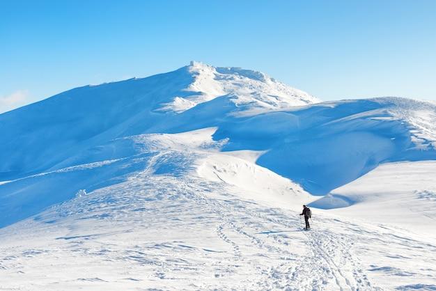 Un uomo che fa un'escursione in montagna d'inverno con la neve bianca sulle cime