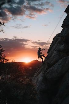 Uomo sulla trentina che si fa un selfie al tramonto mentre si arrampica. verticale