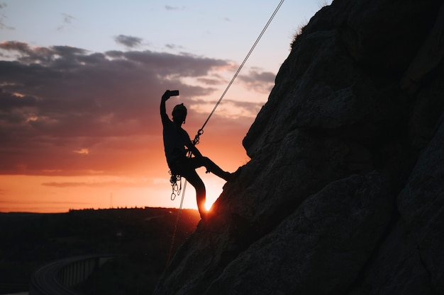 Uomo di 30 anni che si fa un selfie al tramonto mentre si arrampica