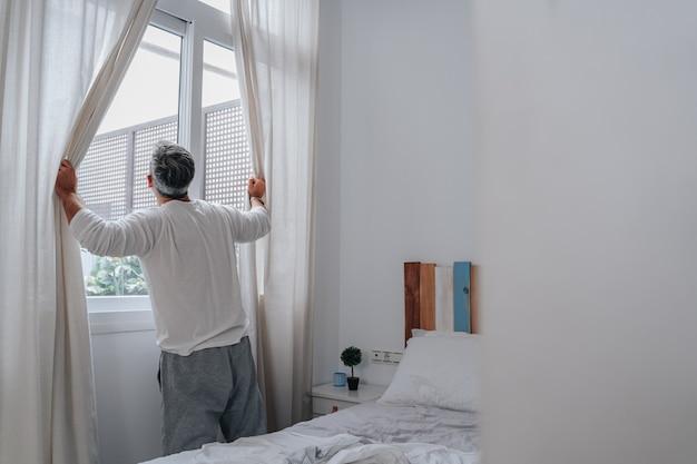 Un uomo sulla cinquantina si è appena svegliato aprendo la finestra