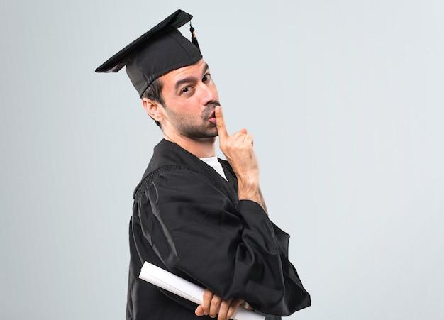 L'uomo nel suo giorno di laurea università che mostra un segno di chiusura bocca e silenzio gesto