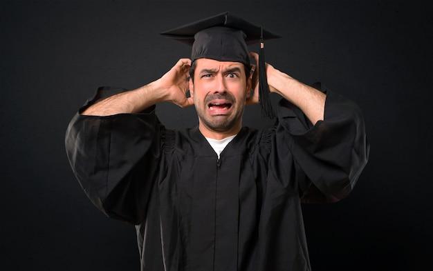 L'uomo nella sua giornata di laurea l'università prende le mani sulla testa perché ha l'emicrania su sfondo nero