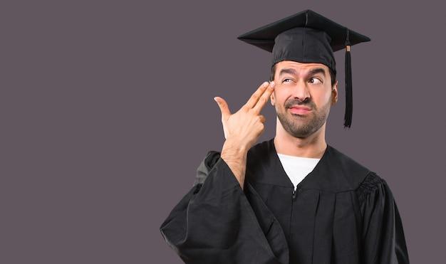 Uomo nel suo giorno di laurea università con problemi e con espressione infelice