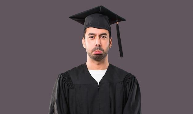 Uomo nel suo giorno di laurea università con espressione triste e depresso. gesto serio