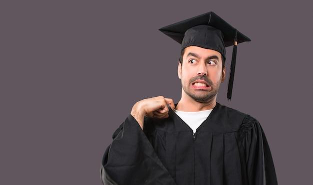 Uomo nel suo giorno di laurea università con espressione stanco e malato su sfondo viola