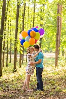 L'uomo e la moglie incinta con palloncini all'aperto
