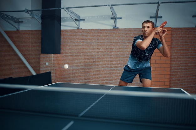 L'uomo colpisce la palla, tennis da tavolo, giocatore di ping pong