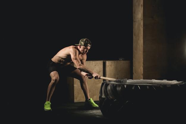 L'uomo colpisce la gomma. allenamento in palestra con martello e trattore siluet pneumatici