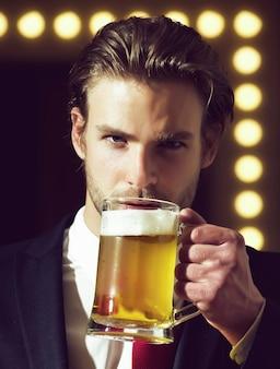 L'uomo tiene il bicchiere di birra con eccellente liquido lager e schiuma densa, ragazzo barbuto soddisfatto in abiti stile ufficio al ristorante, sommelier