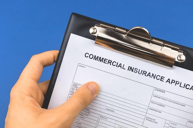 Man tenere appunti con l'applicazione di assicurazione commerciale in mano. foto di sfondo blu