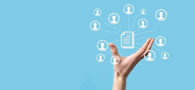 Man tenere documento e icona utente. sistema di gestione dei dati aziendali dms e concetto di sistema di gestione dei documenti. l'uomo d'affari fa clic o pubblica su un documento collegato agli utenti aziendali