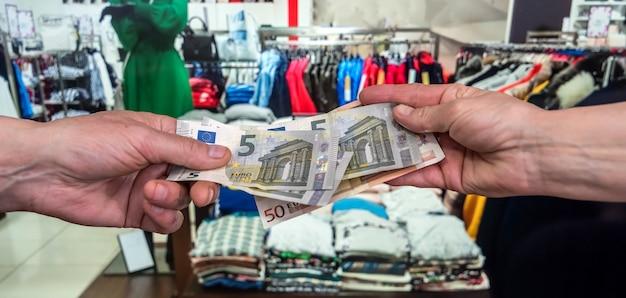 L'uomo tiene le banconote in euro nel negozio di abbigliamento. concetto di acquisto