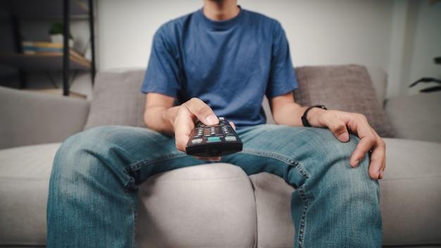 L'uomo tiene e preme il pulsante del telecomando della tv seduto sul divano.
