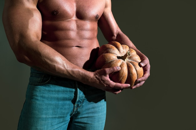 L'uomo tiene l'uomo sexy della zucca con il corpo muscoloso e il concetto di halloween del torso nudo