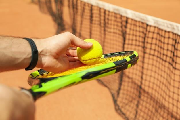 Uomo tenere la racchetta con la pallina da tennis contro il campo in terra battuta