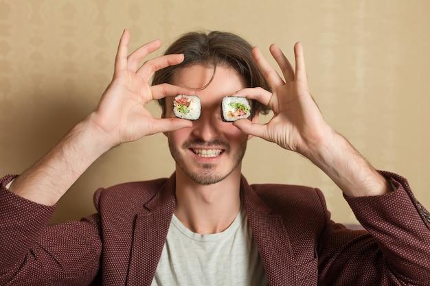 L'uomo tiene i rotoli di sushi invece degli occhi